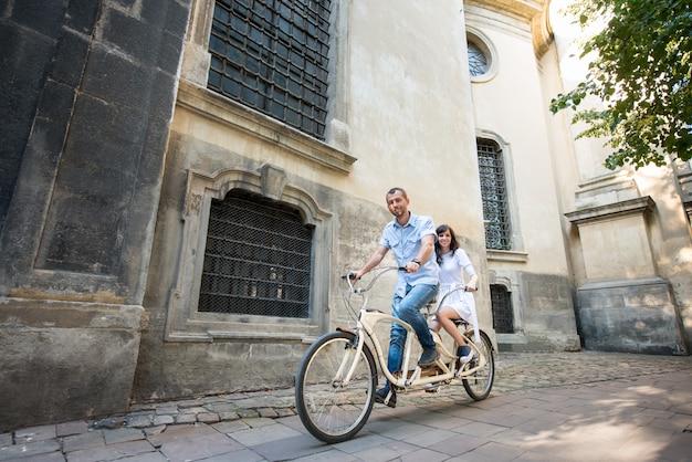 Jeune couple en vélo tandem rétro dans la rue city Photo Premium