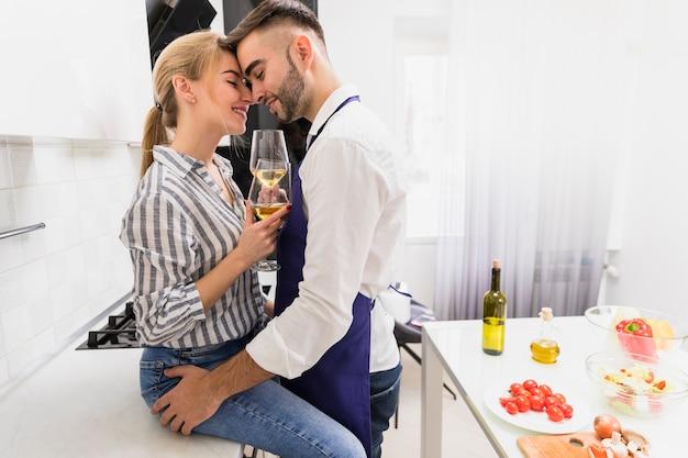 Jeune couple, à, verres vin, étreindre, dans, cuisine Photo gratuit