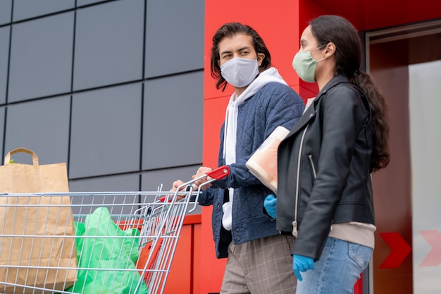 Jeune Couple En Vestes Et Masque En Tissu Quittant Le Supermarché Ensemble Après Le Shopping, Homme Poussant Le Panier Photo Premium
