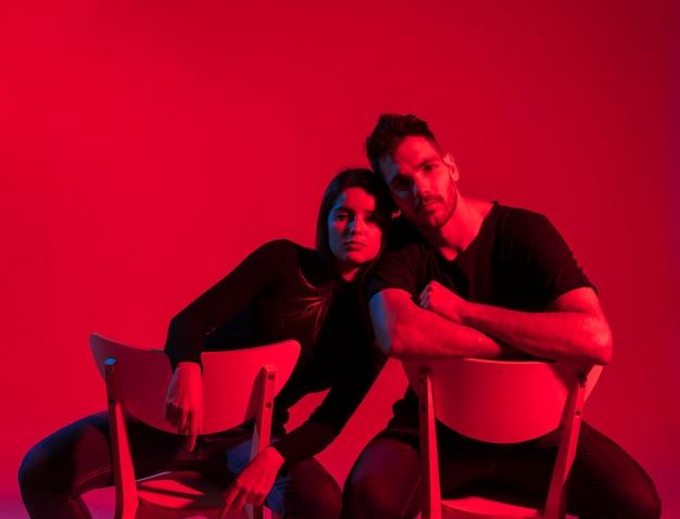 Jeune couple en vêtements noirs assis sur des chaises Photo gratuit