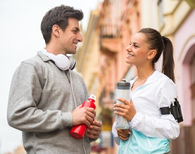 Jeune couple en vêtements de sport avec des bouteilles d'eau. Photo Premium