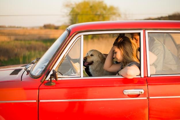 Jeune couple en voiture avec leur chien Photo gratuit