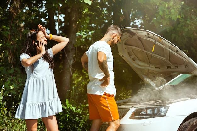 Jeune Couple Voyageant Sur La Voiture En Journée Ensoleillée Photo gratuit