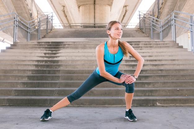 Jeune coureur féminin fitness qui s'étend de jambes avant la course Photo gratuit