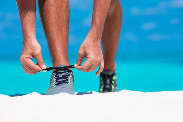 Jeune coureur masculin se prépare pour commencer sur la plage blanche Photo Premium