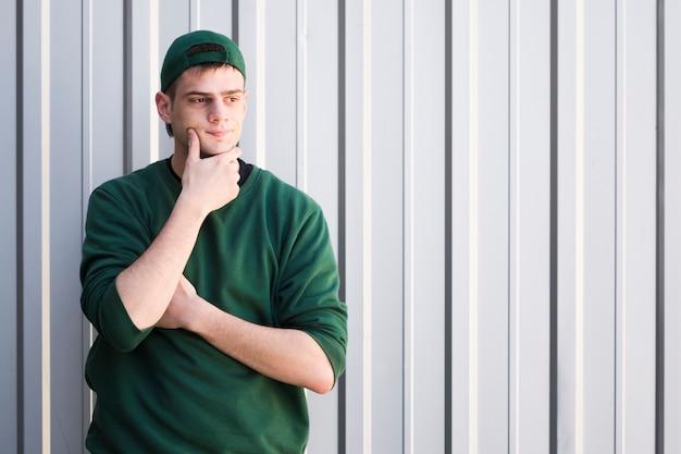 Jeune courrier en bonnet vert touchant le menton Photo gratuit