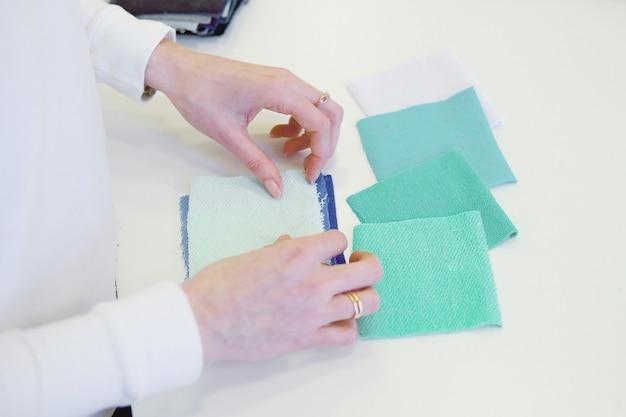 Jeune couturière choisissant un matériau du catalogue en studio. personnaliser la recherche de tissus en position debout dans un atelier de couture Photo Premium