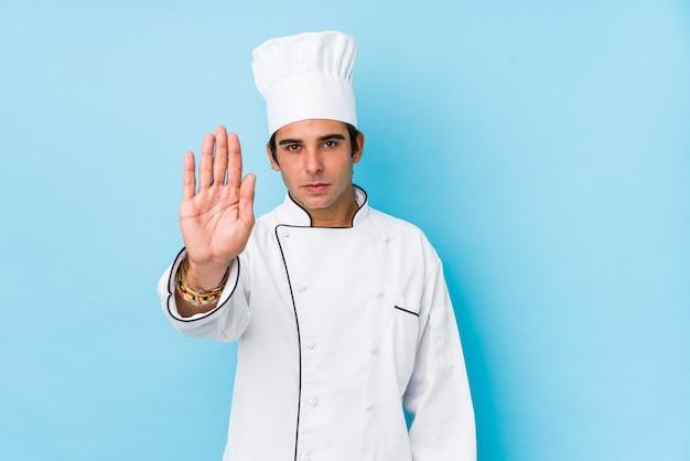 Jeune Cuisinier Homme Isolé Debout Avec La Main Tendue Montrant Le Panneau D'arrêt, Vous Empêchant. Photo Premium