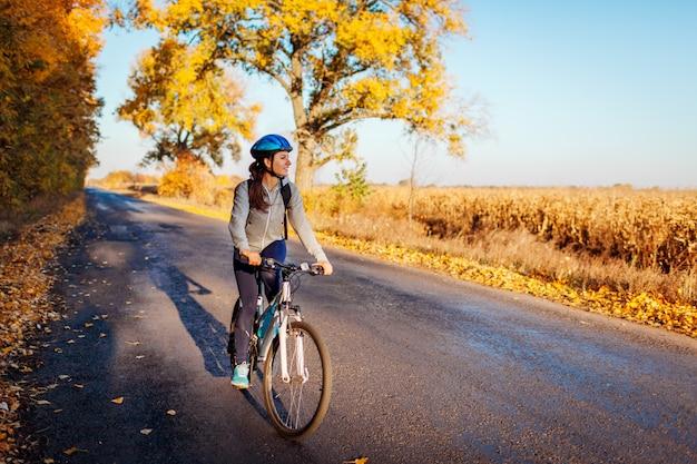Jeune cycliste à cheval sur la route de campagne automne au coucher du soleil, femme heureuse en voyage Photo Premium