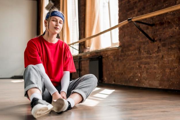 Jeune danseuse assise sur le sol en prenant une pause de la danse Photo gratuit