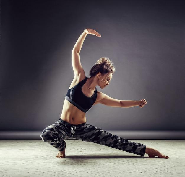 Jeune danseuse mince en vêtements de sport sautant haut sur le mur Photo Premium