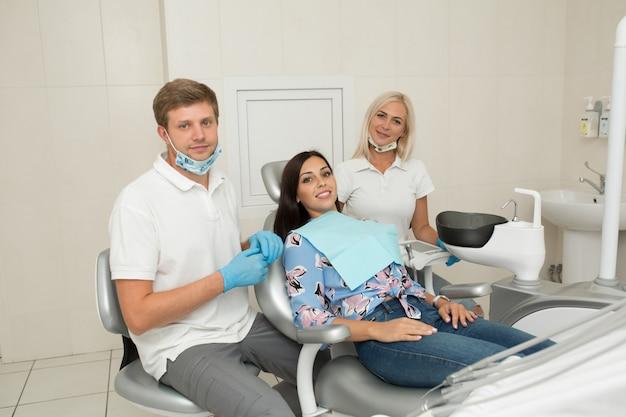 Un Jeune Dentiste Et Une Patiente Heureuse. Scène De Vie De Bureau De Dentiste. Pratique Du Docteur. Soins De Santé Des Patients Photo Premium