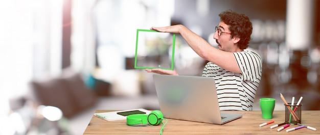 Jeune designer graphique fou sur un bureau avec un ordinateur portable Photo Premium