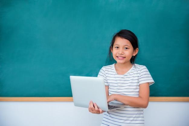 Jeune, écolière asiatique, tenue, ordinateur portable, et, sourires, devant, tableau Photo Premium