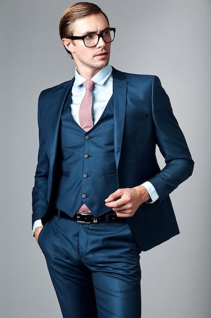 Jeune élégant Modèle Masculin Beau Homme D'affaires En Costume Bleu Et Lunettes à La Mode, Qui Pose En Studio Photo gratuit
