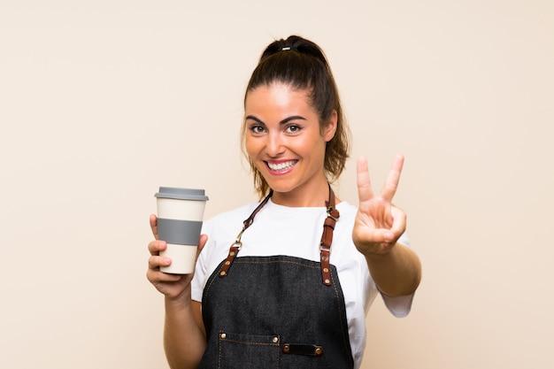 Jeune employé femme tenant un café à emporter souriant et montrant le signe de la victoire Photo Premium
