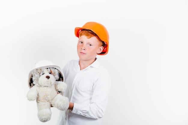 Jeune enfant avec casque de sécurité et ours en peluche Photo gratuit