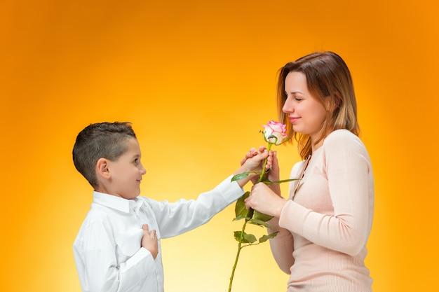 Jeune Enfant Donnant Une Rose Rouge à Sa Maman Photo gratuit