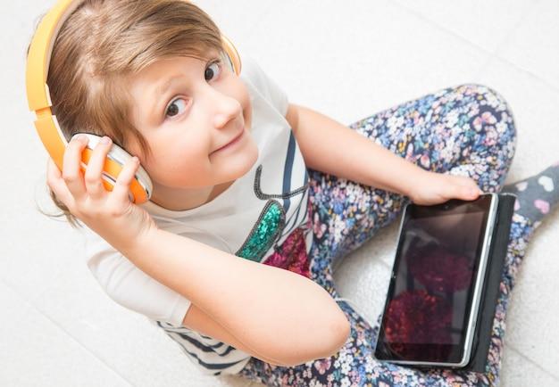 Jeune enfant écoute de la musique avec un casque sur tablette Photo Premium