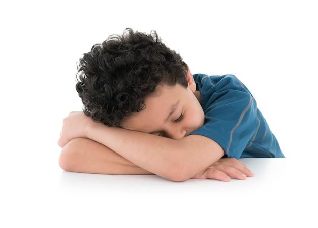 Jeune Enfant Fatigué Dormant Sur Ses Bras Photo Premium