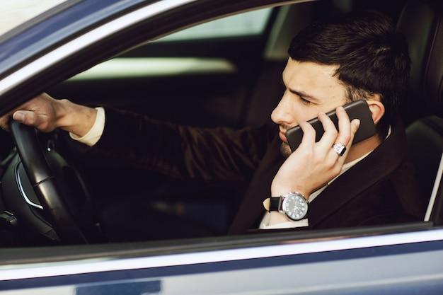 Jeune entrepreneur en costume parle par téléphone dans sa voiture. bussines regardent. essai routier de la nouvelle voiture Photo Premium