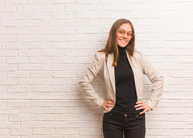 Jeune entrepreneur femme d'affaires avec les mains sur les hanches Photo Premium