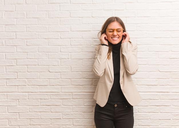 Jeune entrepreneur femme jolie couvrant les oreilles avec les mains Photo Premium