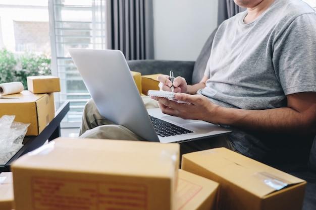 Jeune entrepreneur pme freelance travaillant avec des emballages de billets, livreur de boîtes de tri Photo Premium