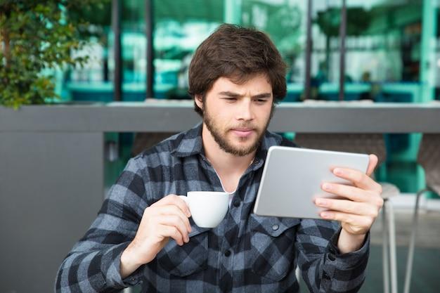 Un jeune entrepreneur sérieux vérifie l'actualité économique Photo gratuit