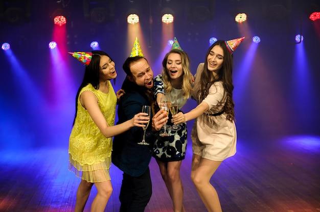 Jeune entreprise joyeuse fête son anniversaire dans une discothèque. Photo Premium