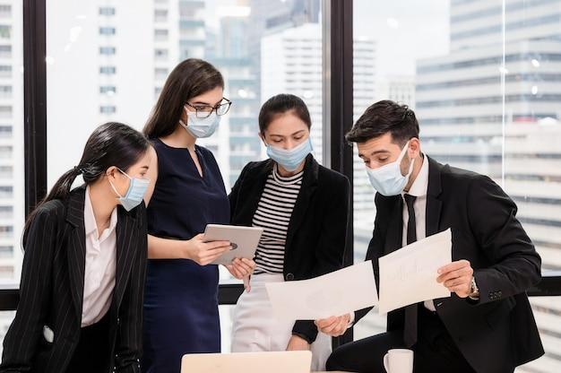 Jeune équipe Commerciale Multiethnique Portant Un Masque Facial Réunion Et Discussion Du Plan D'affaires Au Bureau Photo Premium
