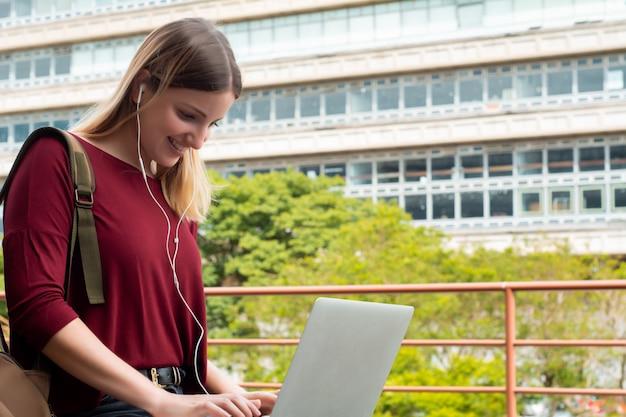 Jeune étudiant à L'aide D'un Ordinateur Portable à L'extérieur. Photo Premium