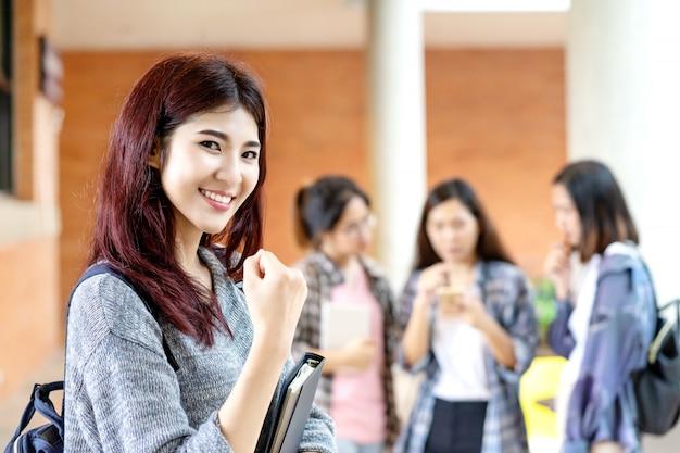 Jeune étudiant asiatique attrayant heureux souriant à la caméra Photo Premium