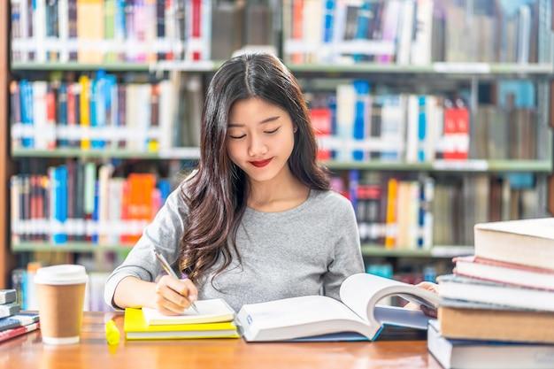 Jeune étudiant Asiatique En Costume Décontracté Lisant Et Faisant Ses Devoirs Dans La Bibliothèque De L'université Photo Premium