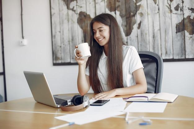 Jeune étudiant assis à la table et utilise son ordinateur portable Photo gratuit