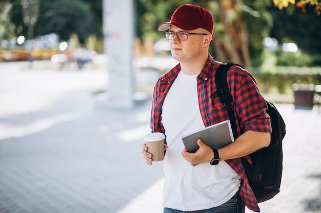 Jeune étudiant, boire du café avec ordinateur portable dans le parc Photo gratuit