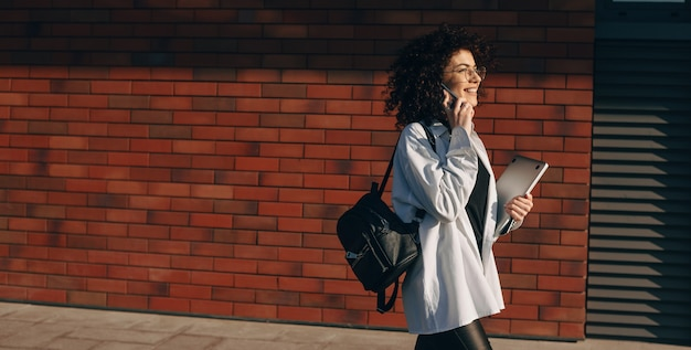 Jeune étudiant Caucasien Aux Cheveux Bouclés Parle Au Téléphone Tout En Marchant Avec Un Sac Et Un Ordinateur Portable Photo Premium