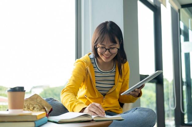 Jeune étudiant en collage à l'aide d'un ordinateur et d'un appareil mobile, étudie en ligne. Photo Premium