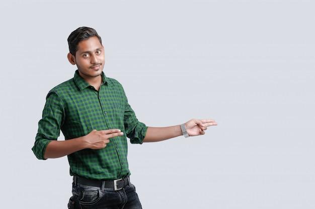 Jeune étudiant indien indiquant la direction Photo Premium