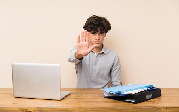 Jeune étudiant avec un ordinateur portable faisant un geste d'arrêt Photo Premium