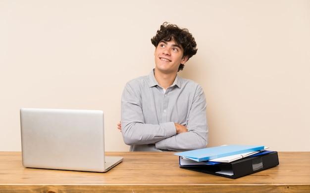 Jeune étudiant avec un ordinateur portable en levant tout en souriant Photo Premium