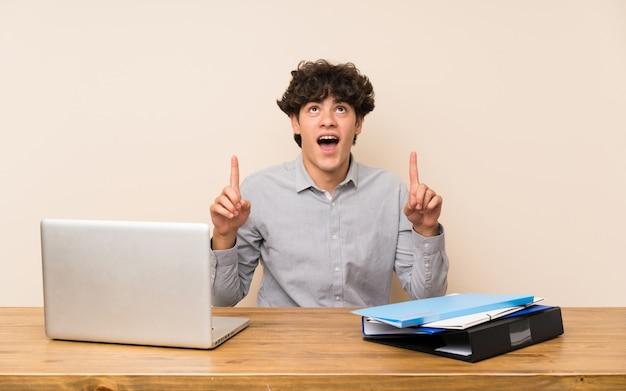 Jeune étudiant avec un ordinateur portable surpris et pointant vers le haut Photo Premium