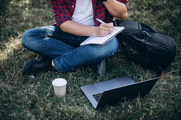 Jeune étudiant travaillant sur un ordinateur dans le parc Photo gratuit
