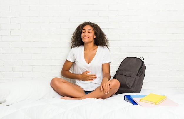 Jeune étudiante afro-américaine sur le lit touche le ventre, sourit doucement, concept de manger et de satisfaction. Photo Premium