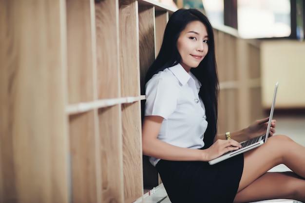 Jeune étudiante à l'aide d'un ordinateur portable à la bibliothèque Photo gratuit