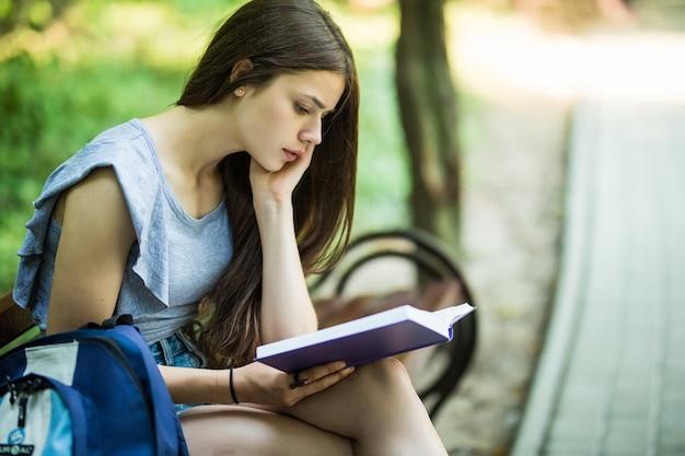 Jeune étudiante Assise Sur Un Banc Et Livre De Lecture Dans Le Parc Photo gratuit