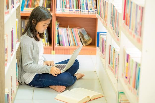 Jeune étudiante assise dans une bibliothèque Photo gratuit