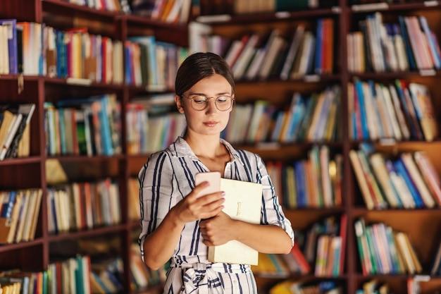 Jeune étudiante Attrayante Debout Dans La Bibliothèque, Tenant Un Livre Et Utilisant Un Téléphone Intelligent. Photo Premium