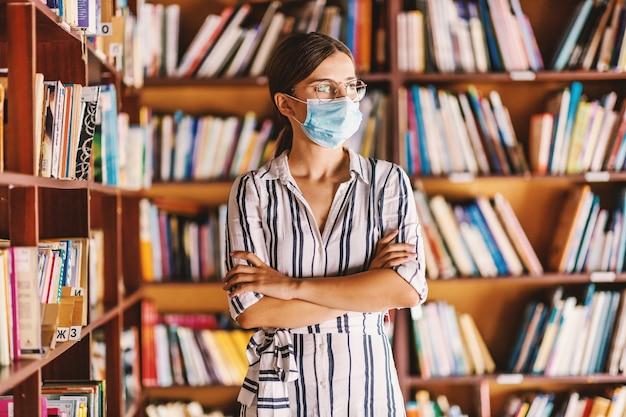 Jeune étudiante Attrayante Intelligente Avec Masque Facial Debout Dans La Bibliothèque Avec Les Bras Croisés Photo Premium