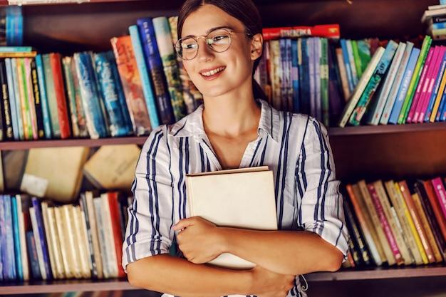 Jeune étudiante Attrayante En Robe Debout Dans La Bibliothèque Devant Des étagères Avec Des Livres Et Tenant Son Roman Préféré. Photo Premium